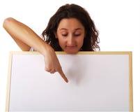 Jeune femme retenant un panneau blanc image stock