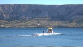 Jeune femme retirée par le ski de hors-bord et d'eau sur l'eau et les vagues sur la mer, océan banque de vidéos