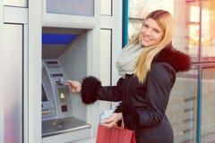 Jeune femme retirant l'argent de la carte de crédit au distributeur automatique de billets d'atmosphère image libre de droits