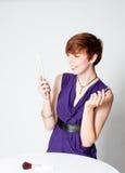Jeune femme riant appliquant le rouge à lievres Photographie stock libre de droits