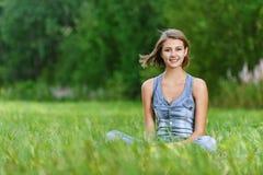 Jeune femme riant s'asseyant en fonction Photographie stock
