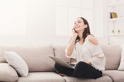 Jeune femme riante à la maison avec l'ordinateur portable et le mobile Image libre de droits