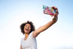 Jeune femme riante d'afro-américain prenant le selfie avec le téléphone intelligent dehors images stock