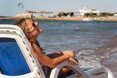 Jeune femme riante dans des lunettes de soleil se reposant dans une chaise longue, encore Image stock