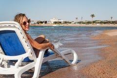 Jeune femme riante dans des lunettes de soleil se reposant dans une chaise longue, encore Images libres de droits