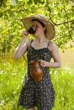 Jeune femme romantique buvant dans le jardin Photographie stock libre de droits