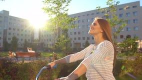 Jeune femme romantique heureuse faisant un cycle heureusement par une rue ensoleillée dans l'été dehors Bicyclette d'équitation d clips vidéos