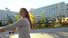 Jeune femme romantique heureuse faisant un cycle heureusement par une rue ensoleillée dans l'été dehors Bicyclette d'équitation d banque de vidéos