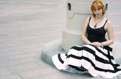 Jeune femme rouge en noir et blanc rayé épanoui Image stock