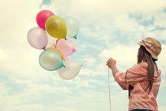 Jeune femme rouge heureuse de cheveux tenant les ballons colorés et volant sur le fond de ciel de nuages Photos libres de droits