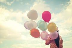 Jeune femme rouge heureuse de cheveux tenant les ballons colorés et volant sur le fond de ciel de nuages Image stock