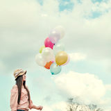 Jeune femme rouge heureuse de cheveux tenant les ballons colorés et volant sur le fond de ciel de nuages Photographie stock