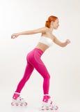 Jeune femme rouge sur des patins de rouleau Photographie stock libre de droits