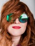 Jeune femme rousse élégante avec les cheveux bouclés et joli le visage posant dans des lunettes de soleil exprime différentes émo Images stock