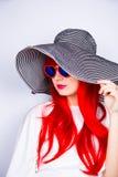 Jeune femme rousse attirante dans les lunettes de soleil et le chapeau sur le blanc Image libre de droits