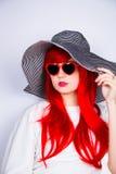 Jeune femme rousse attirante dans les lunettes de soleil et le chapeau sur le blanc Images libres de droits