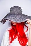 Jeune femme rousse attirante dans les lunettes de soleil et le chapeau sur le blanc Photos libres de droits