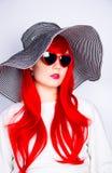 Jeune femme rousse attirante dans les lunettes de soleil et le chapeau sur le blanc Photo stock