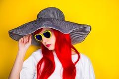 Jeune femme rousse attirante dans les lunettes de soleil et le chapeau sur le yello Image libre de droits