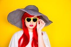 Jeune femme rousse attirante dans les lunettes de soleil et le chapeau sur le yello Photographie stock