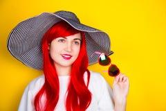 Jeune femme rousse attirante dans les lunettes de soleil et le chapeau sur le yello Image stock