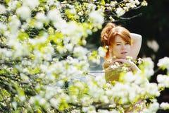 Jeune femme rousse au printemps Image stock