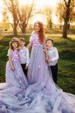 Jeune femme rousse avec ses enfants dans des vêtements intelligents se tenant en parc Photographie stock libre de droits