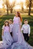 Jeune femme rousse avec ses enfants dans des vêtements intelligents se tenant en parc Images stock