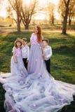 Jeune femme rousse avec ses enfants dans des vêtements intelligents se tenant en parc Image stock