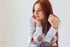 Jeune femme rousse dans la chemise blanche image stock