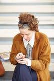 Jeune femme rousse de hippie à l'aide du smartphone Images stock