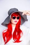 Jeune femme rousse de sourire attirante dans les lunettes de soleil et le chapeau Photo stock