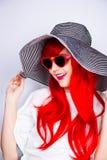 Jeune femme rousse de sourire attirante dans les lunettes de soleil et le chapeau Images stock