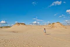 Jeune femme rousse marchant sous le soleil le long des dunes arénacées sans fin Photos libres de droits