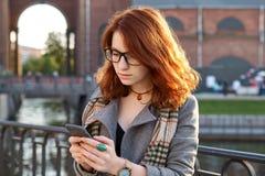 Jeune femme rousse moderne en parc en automne utilisant le téléphone intelligent la fille avec la coiffure bouclée de gingembre,  photos libres de droits