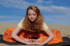 Jeune femme rousse s'asseyant dans la pose de yoga de titli de purna sur le beac Photos stock