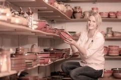 Jeune femme sélectionnant la céramique avec l'émail rouge dans l'atelier Photos libres de droits