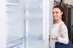 Jeune femme sélectionnant le réfrigérateur ménager dans le magasin d'électro-ménagers Photos libres de droits