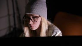 Jeune femme sérieuse à l'aide de l'ordinateur la nuit dans la chambre noire clips vidéos