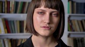 Jeune femme sérieuse avec la coupe de cheveux courte dans la veste se tenant dans la bibliothèque et regardant l'appareil-photo banque de vidéos
