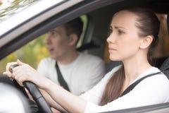 Jeune femme sérieuse conduisant une voiture, homme s'asseyant de côté Image libre de droits