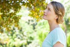 Jeune femme sérieuse regardant des feuilles en parc photo libre de droits