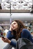 Jeune femme sérieuse s'asseyant à l'aéroport avec le téléphone portable Photos stock