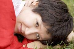 Jeune femme sérieux dans l'écharpe rouge se trouvant sur l'herbe image libre de droits