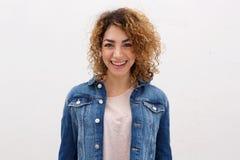 Jeune femme sûre avec le fond blanc de abaissement de sourire de cheveux bouclés Images libres de droits