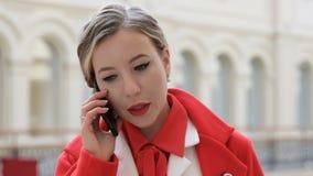 Jeune femme sûre d'affaires dans le manteau rouge parlant au téléphone banque de vidéos