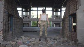 Jeune femme sûre dans l'uniforme militaire marchant lentement dans le bâtiment abandonné sale poussiéreux Femme de guerrier dans  banque de vidéos