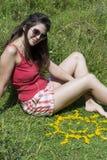 Jeune femme s'étendant sur un pré avec les fleurs jaunes Photo libre de droits