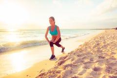 Jeune femme s'étirant sur la plage Image stock