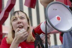 Jeune femme s'adressant à la foule avec le mégaphone au prot de violence armée Photo stock